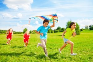 24234068 - group of four little kids, boy and girls running with kite in the park on summer day